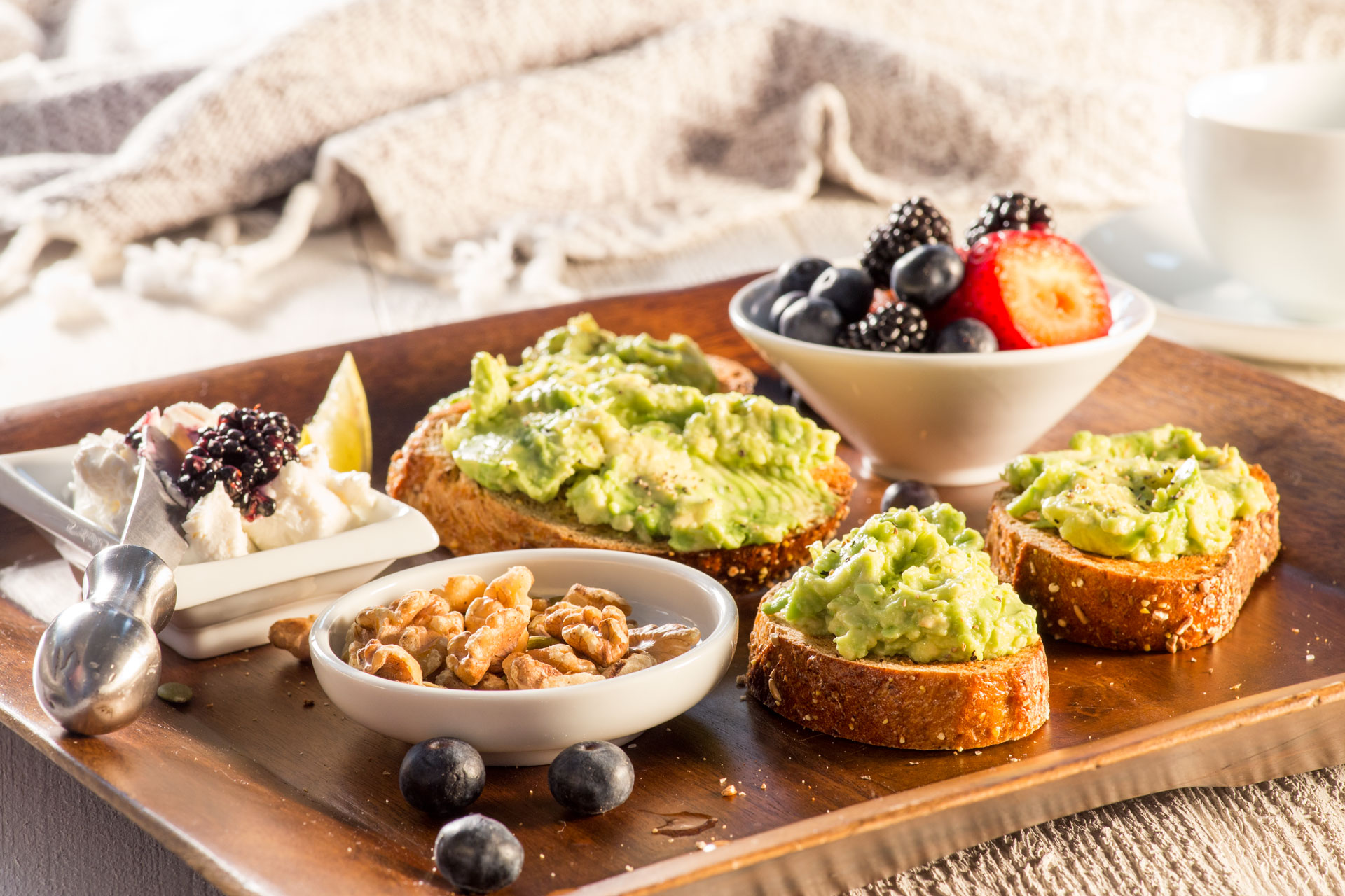 Our non-traditional continental breakfast board includes sprouted whole grain toast with ripe mashed avocado served with an assortment of fresh fruit (the tart tangy flavor of blueberries are particularly delicious paired with avocado), toasted walnuts and cheese.