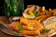 Unlike English fish and chips, which were traditionally served in folded newspaper, these light crispy beer battered fish and chips are served Irish pub-style piled on rustic torn brown paper bags with fresh-made tartar sauce, lemon, and malt vinegar.