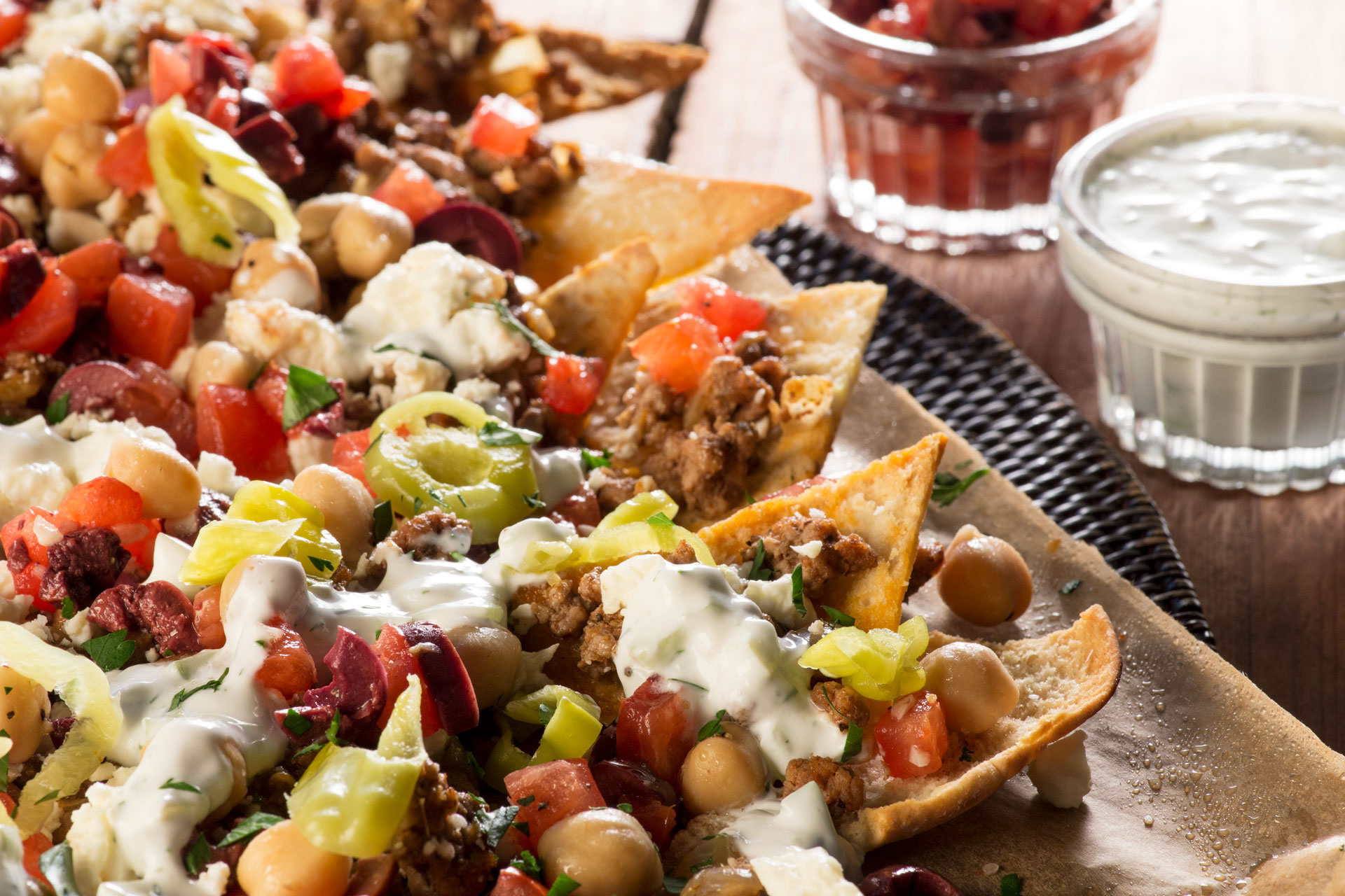 Own Your Party with this epic Greek nachos recipe using Aussie lamb! You'll get spicy Australian lamb served on fresh-baked pita chips with feta cheese, Mediterranean olive pico de gallo and tzatziki sauce.