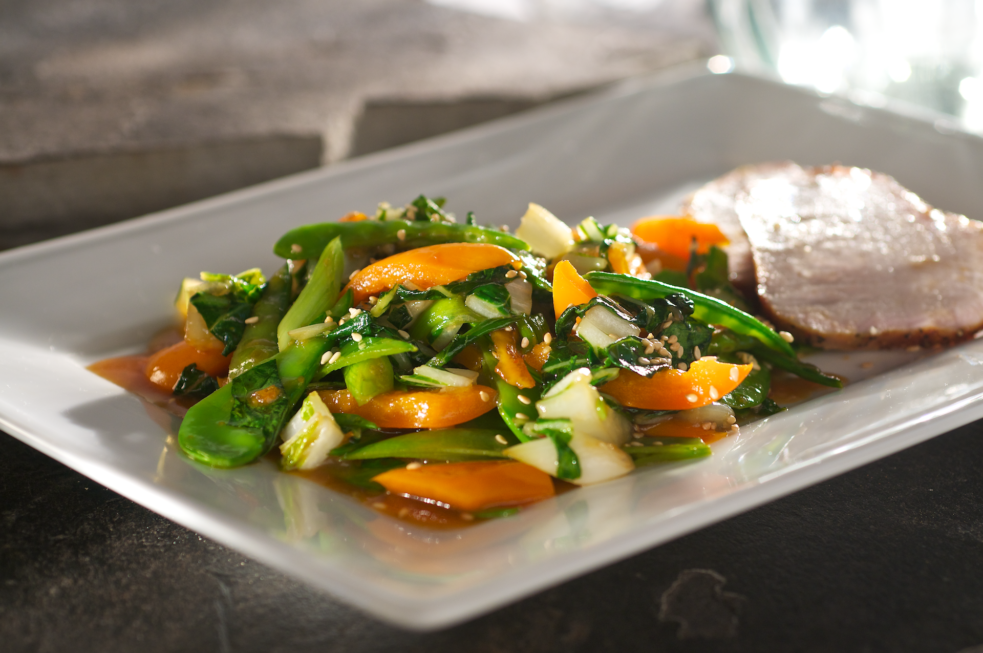 This fresh, colorful Asian vegetable stir-fry features crisp bok choy, snow peas, orange bell pepper and scallions tossed in an aromatic chili orange glaze with ginger and toasted sesame oil.
