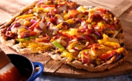 Grilling adds a smoky-sweet flavor to pizza that can't be duplicated in an oven. For this classic BBQ grilled pizza, we layered smoky char-grilled chicken, bell peppers, red onions, sizzling bacon, barbecue sauce and sharp Cheddar cheese on thin crust pizza dough grilled until golden and bubbly.