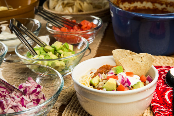 Delicious slow-simmered chili, ladled over your favorite pasta, with an assortment of toppings, including shredded cheddar cheese, fresh chopped tomatoes, diced red onions, sour cream, ripe diced avocados and tortilla chips.