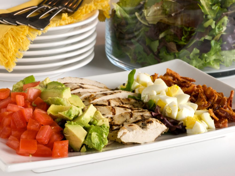 Chef Cari prepares her famous Cobb Salad with avocado, bacon, cherry tomatoes, and chicken.