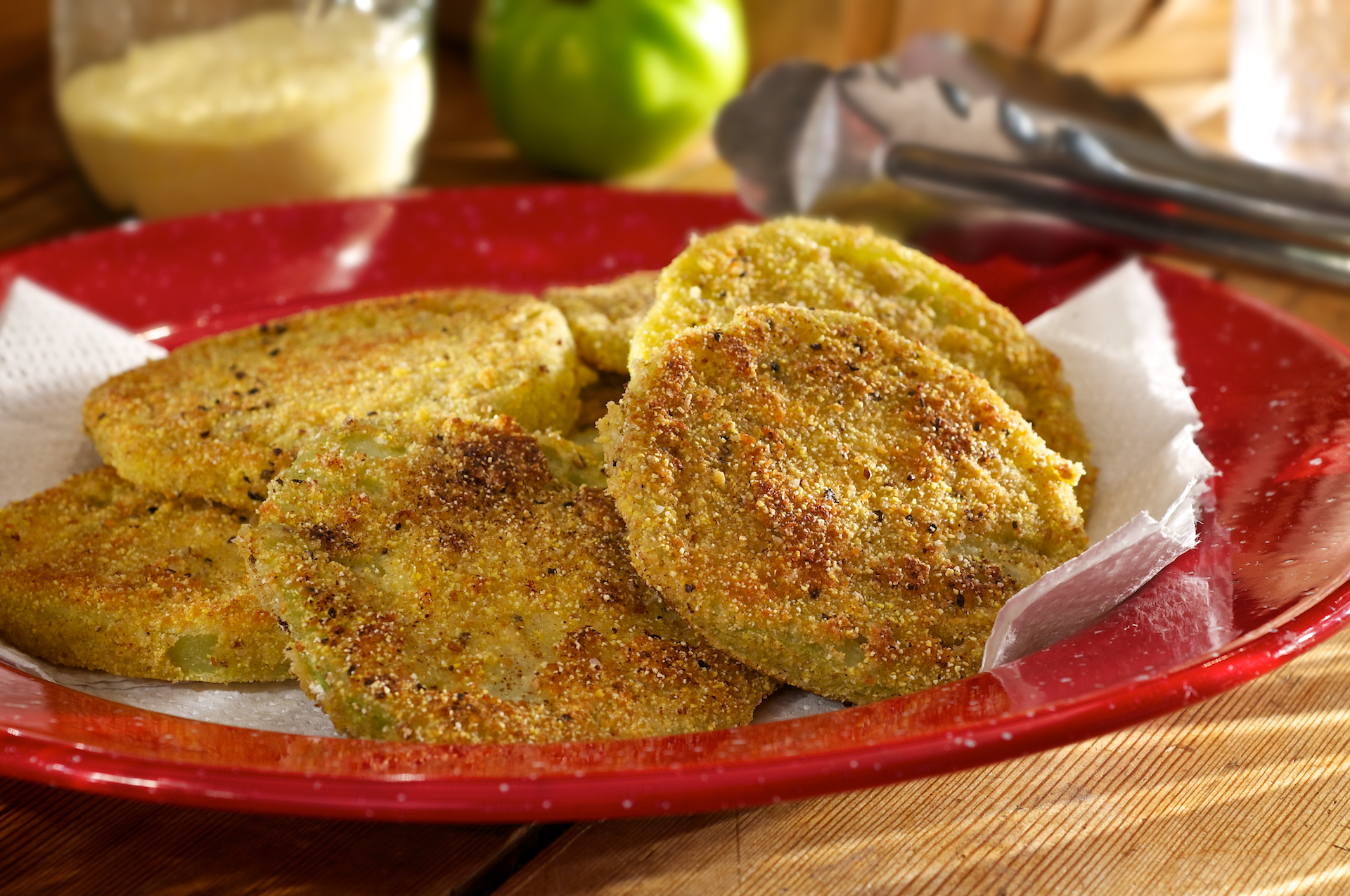 This hearty side dish features thick slices of fresh green tomatoes dipped into egg, flour and cornmeal mixture and pan fried until golden.