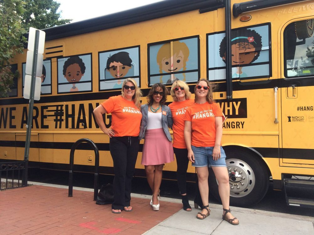 photo of no kid hungry staff standing in front of the no kid hungry tour bus