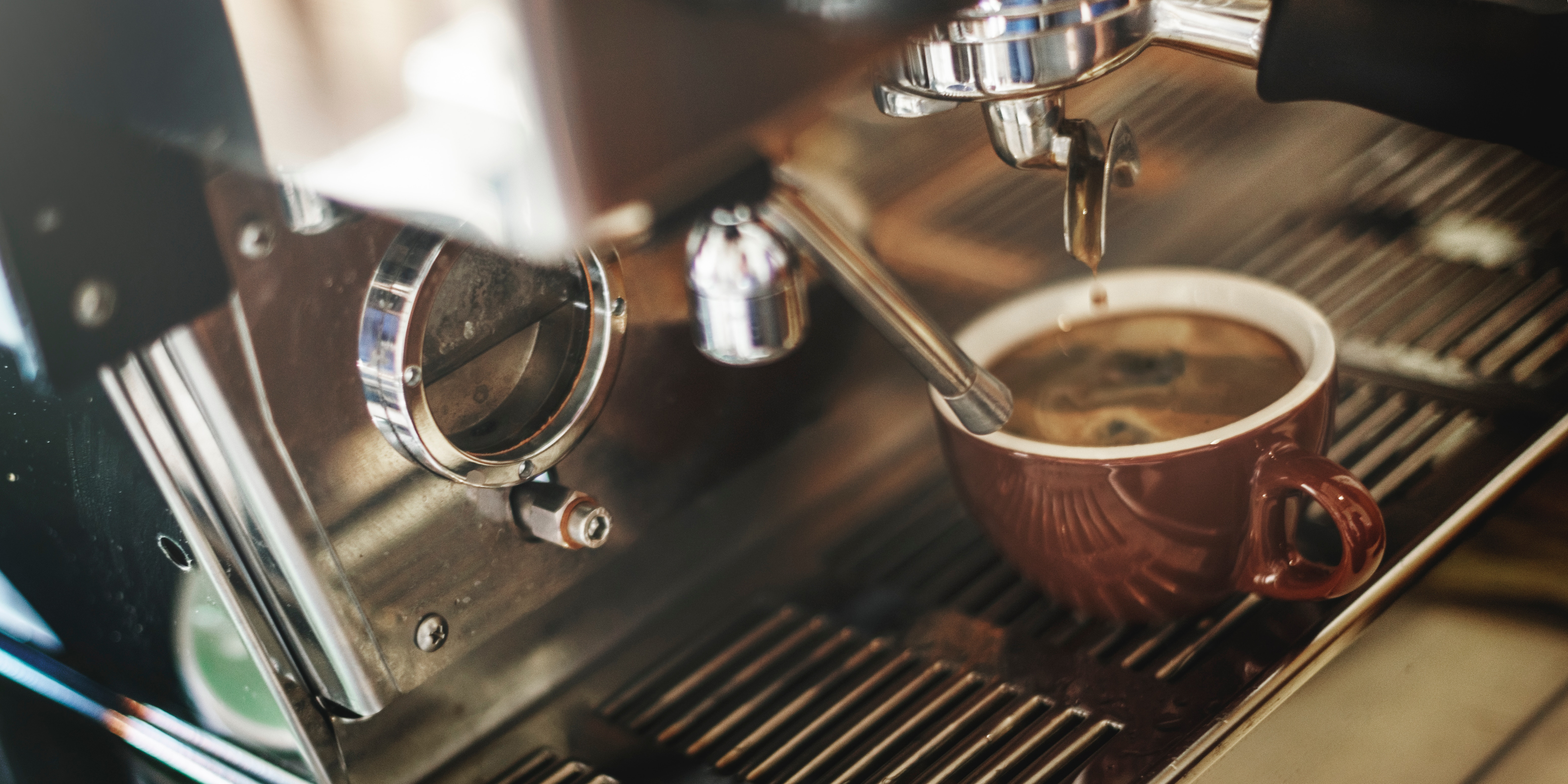 photo of an espresso machine filling a cup with rich coffee