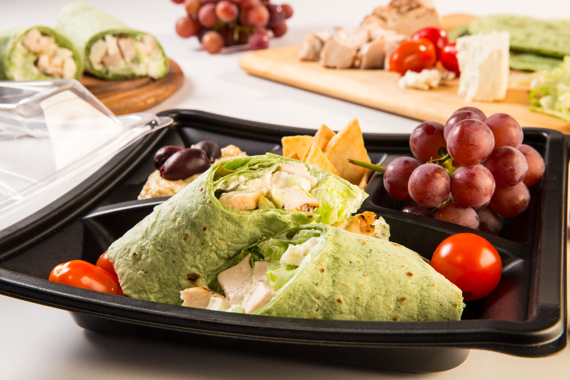 Our healthy Mediterranean-inspired bento box includes a grilled chicken and feta wrap, hummus dip, kalamata olives, crunchy pita chips and fresh grapes.
