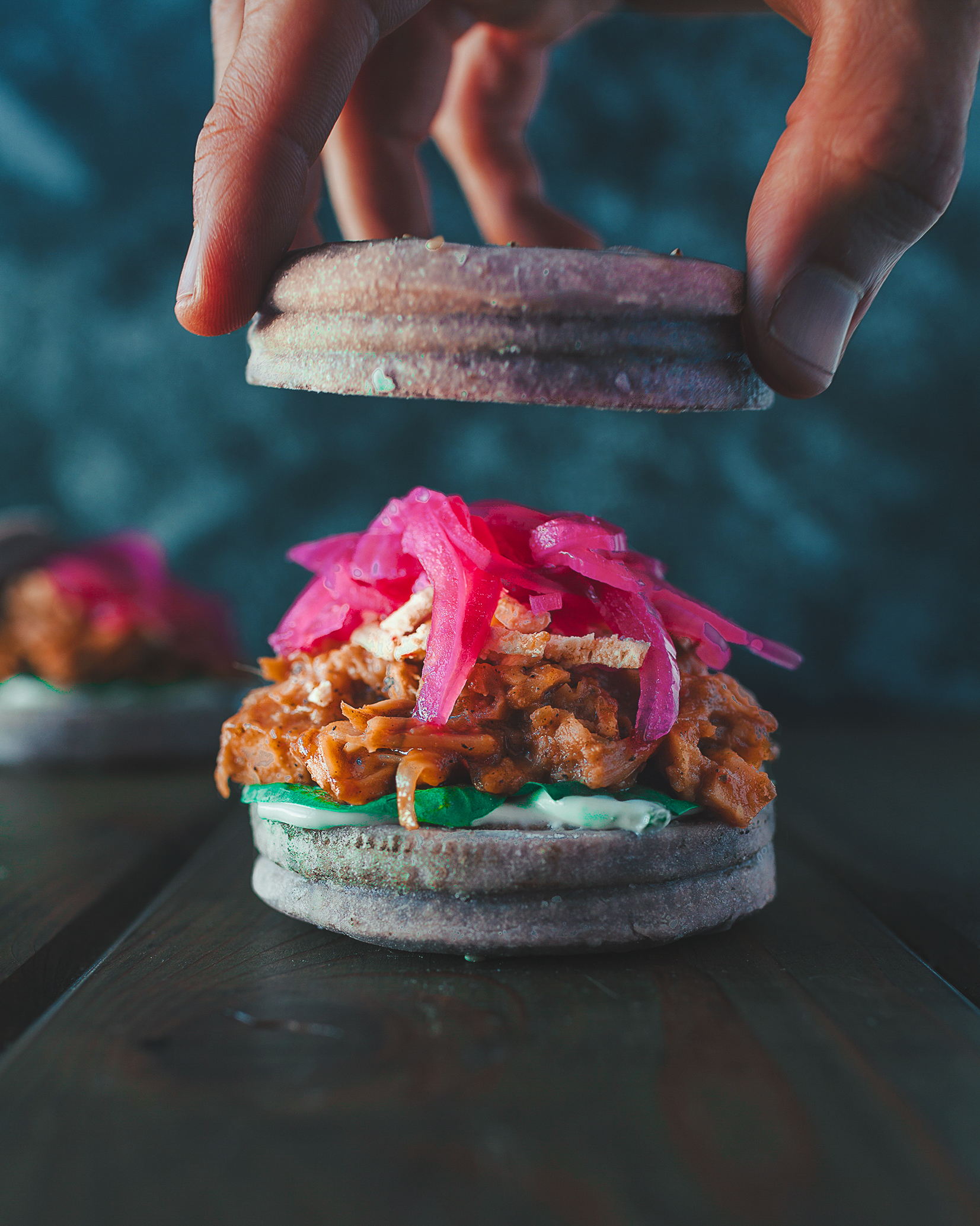 This sandwich features the meaty jackfruit, garlic aioli, pickled red onions, and vegan pepper jack cheese on a black goji berry gluten-free bun. This sandwich is irresistible and packed full of explosive flavor!