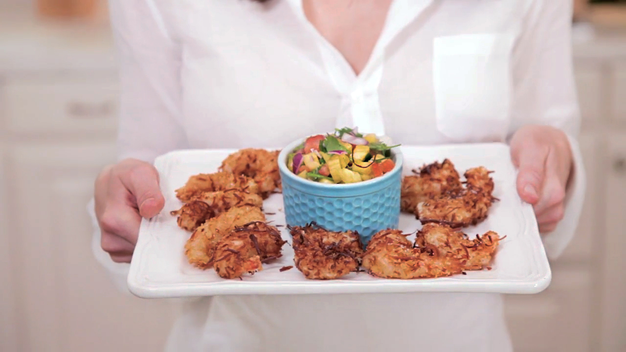 Guest Contributor Roni Proter of Dinner Reinvented shows you how to create crispy coconut shrimp served with fresh pineapple salsa. How-to video here with recipe link included.