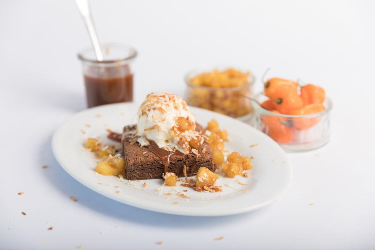 Plated Coconut Habanero Brownie topped with Habanero Peppers, Pineapple, and Caramel Sauce.