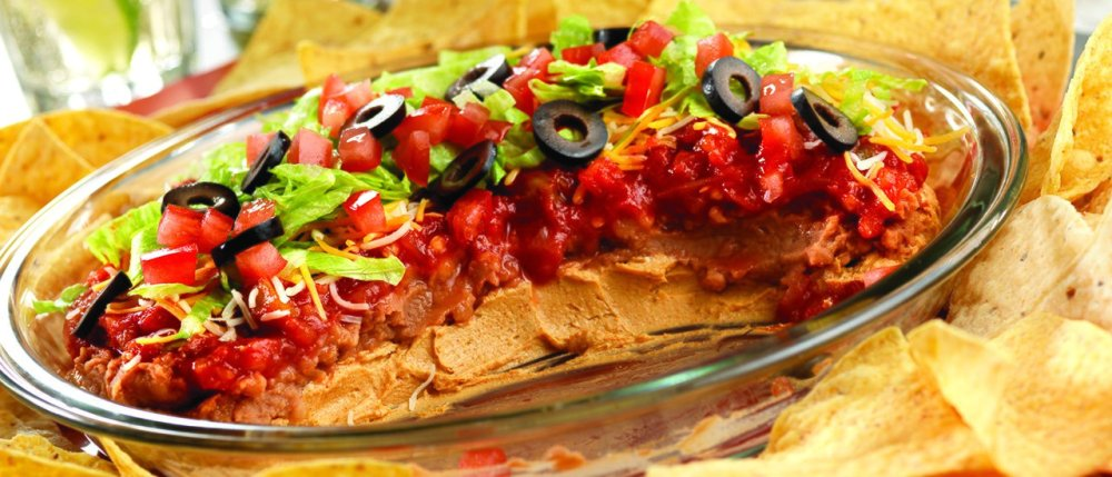 Great for game day and casual gatherings, this kicked-up Southwestern-style seven-layer dip recipe will score big with your guests. A glass pie plate is perfect for this dip, but you can also use a disposable football-shaped dish to enhance the football theme!