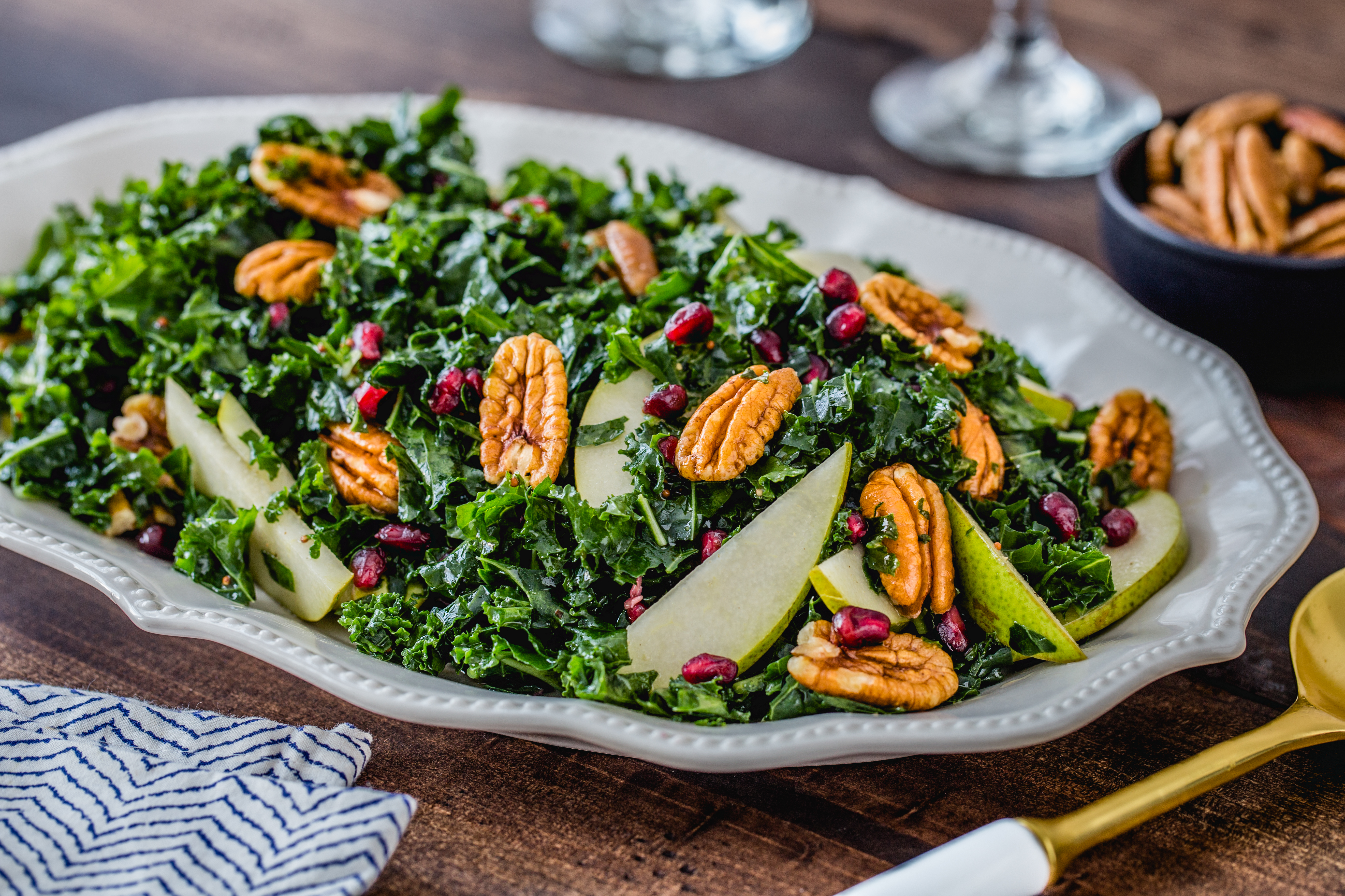 Combine crunchy kale with fresh pecans, pomegranate seeds and pears for a colorful and nutritious salad that's topped with a simple homemade dressing.