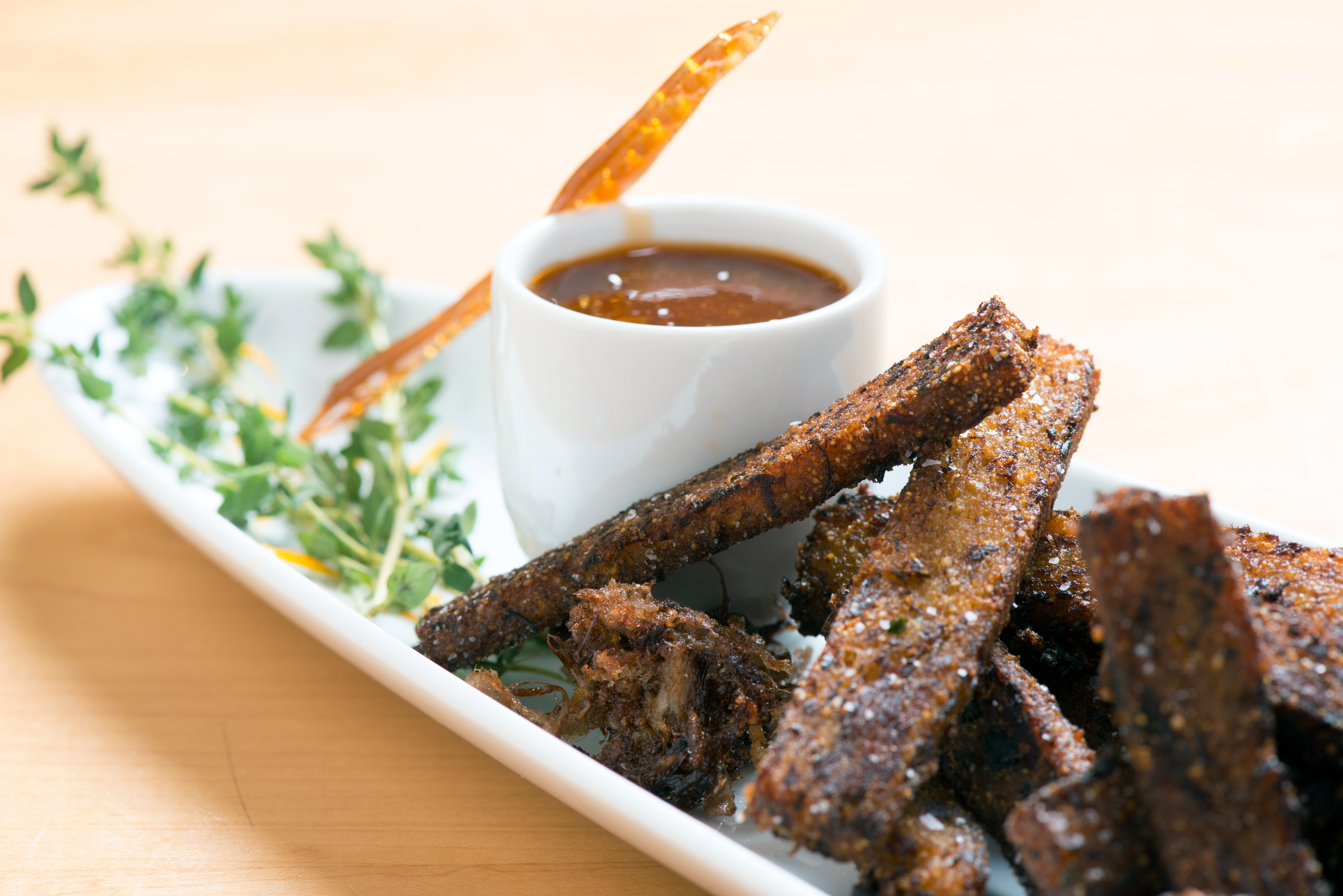These smokey pork'fries' are easy-to-eat, hand-held pork shoulder bites made with apple cider, dijonmustard, buckwheat honey, herbs, spices, and cornmeal.