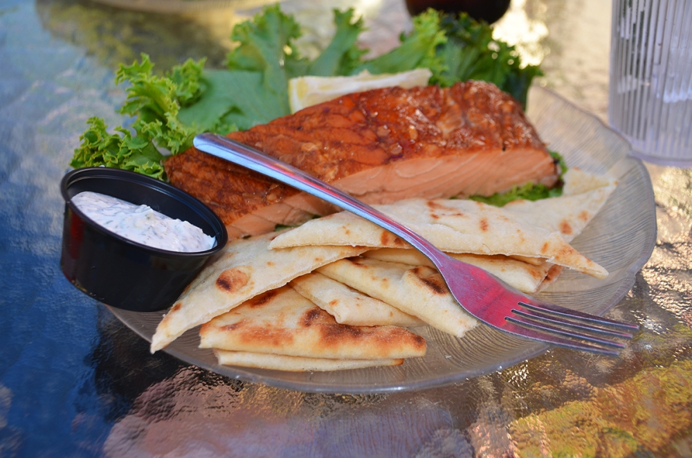 A plate of smoked fish served with pita bread.