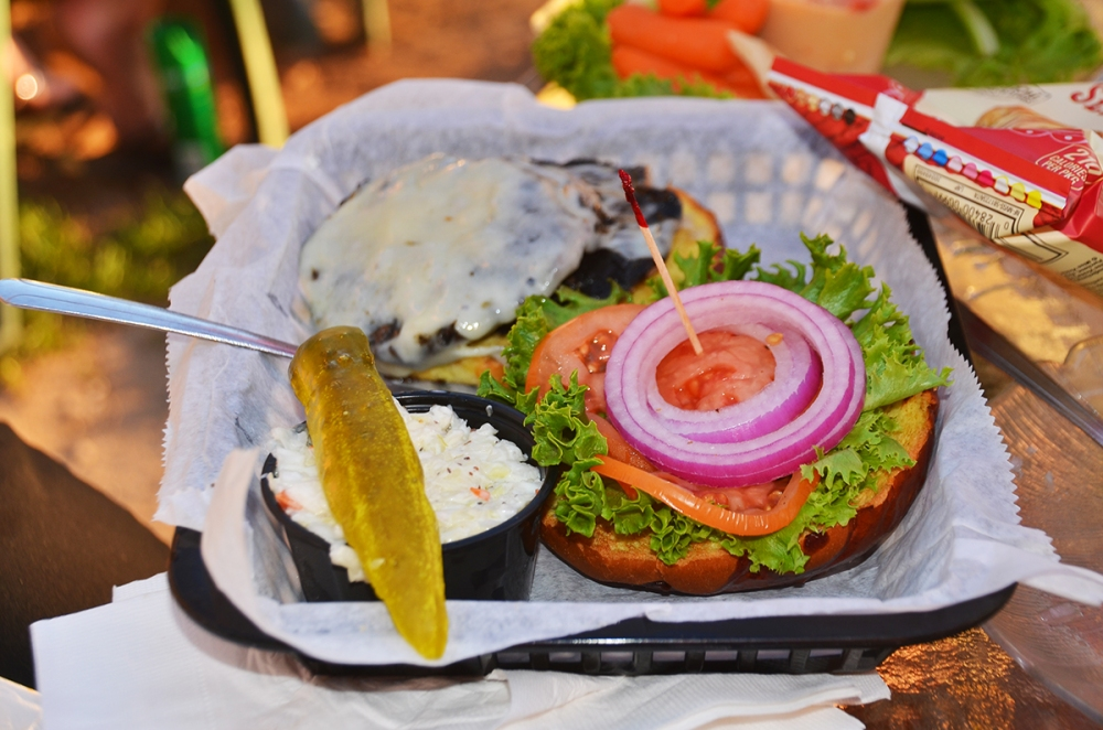 A mouth-watering burger from Fred and Fuzzy's, served with fresh onions, lettuce, tomatoes and a pickle slice.