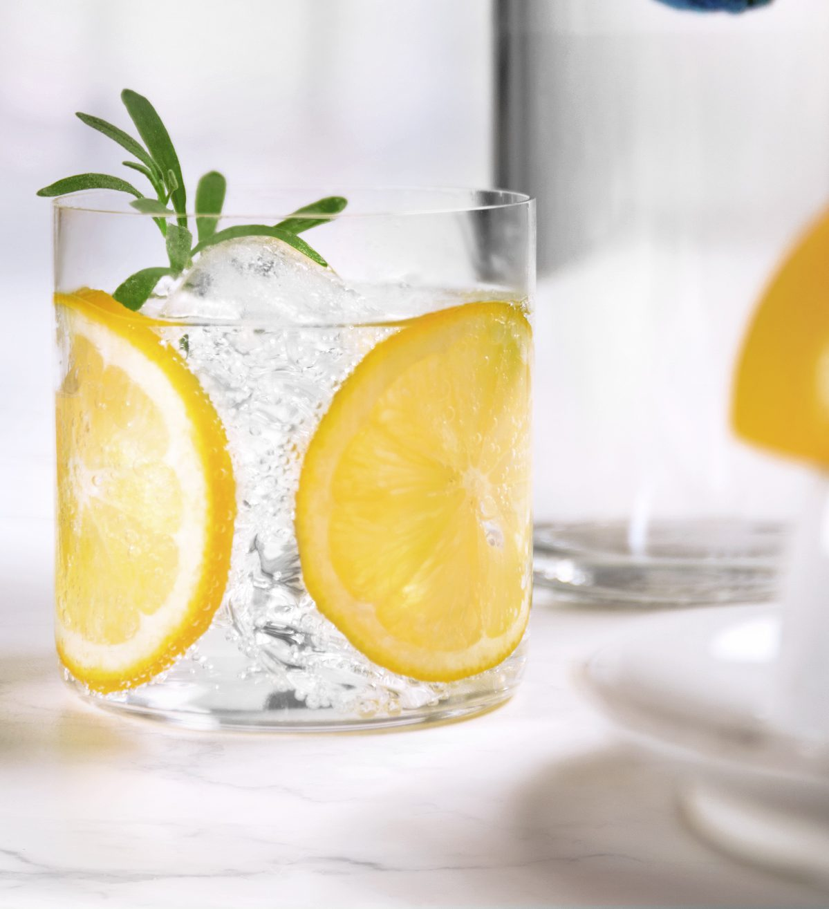Shake first two ingredients well with ice. Strain into a rocks glass over fresh ice and stir in club soda. Top with juice from a squeezed lemon. Garnish with lemon wheel and rosemary sprig.