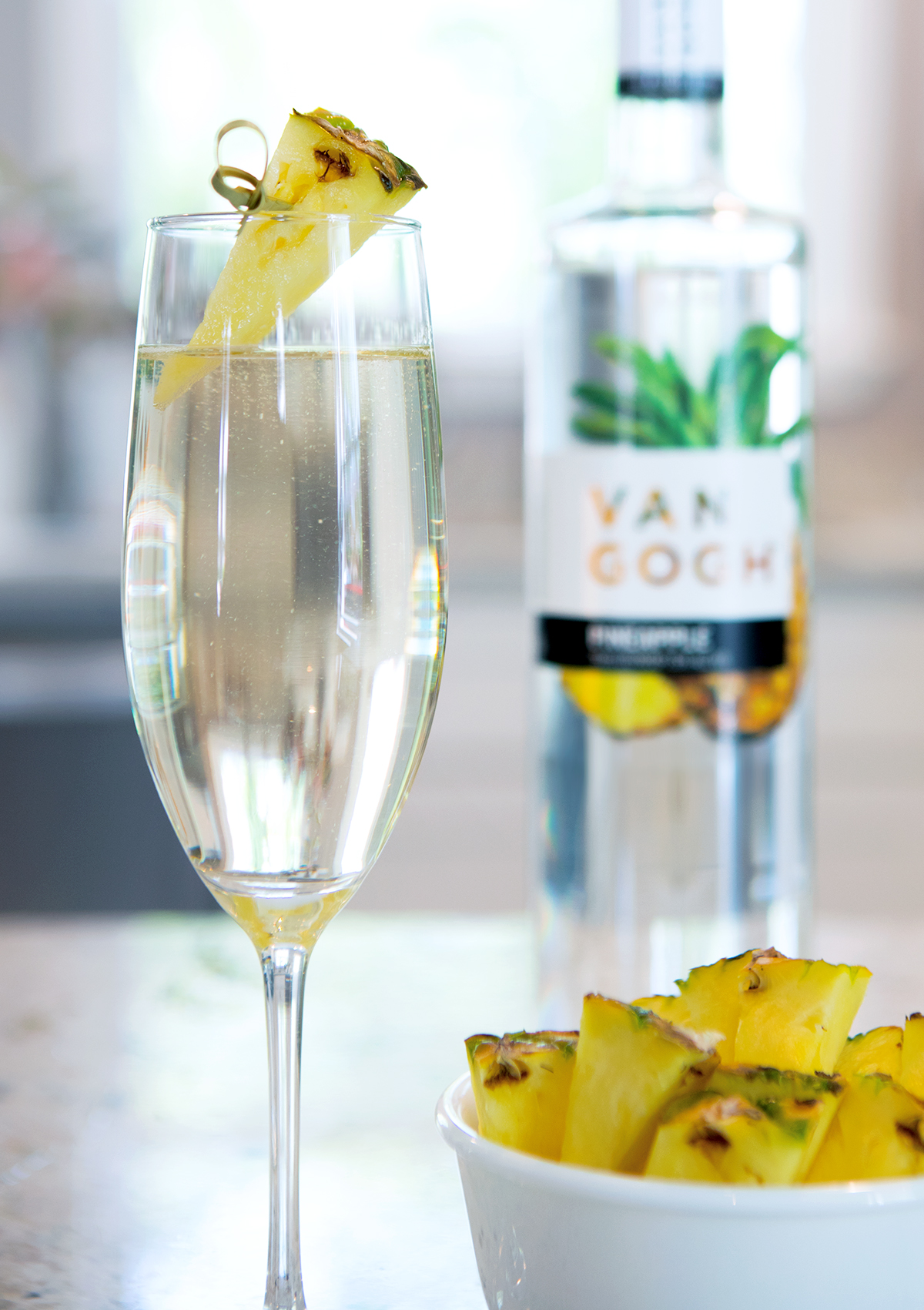 Add chilled pineapple vodka to a flute and top with chilled sparkling wine. Garnish with a. pineapple slice.