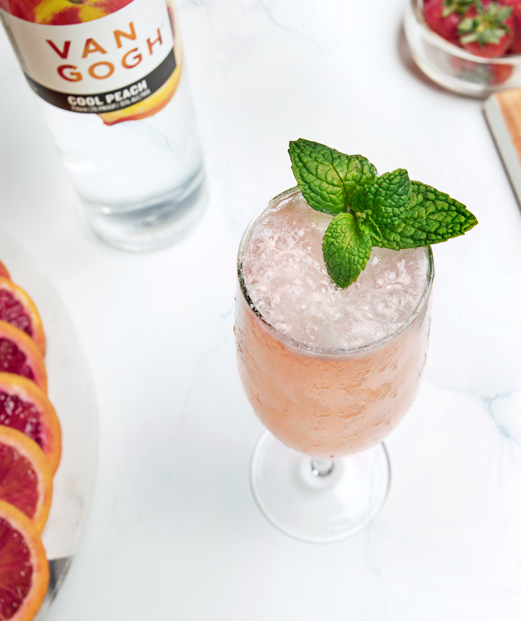 In a mixing glass, add ingredients with ice and gently fold together without over-stirring. Strain into a chilled flute. Garnish with a floating mint leaf and peach slice.