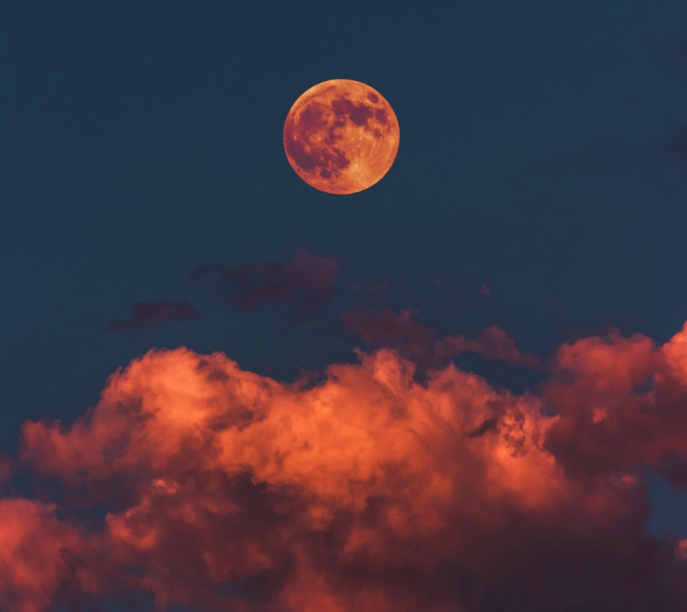 A full moon rises over a cloudy sky, the perfect setting for a Halloween celebration.