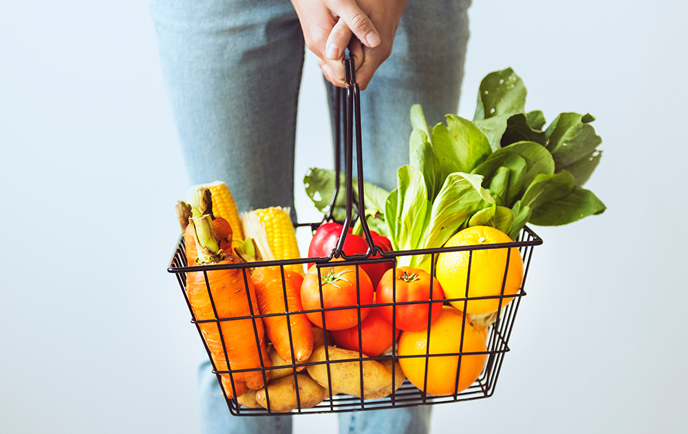 Holding a shopping basket filled with fresh fruit and vegetables.