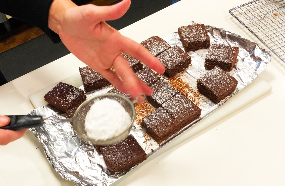Powdered sugar is sprinkled over the a tray of fresh baked brownies, made with Rio Luna organic jalapeño peppers.