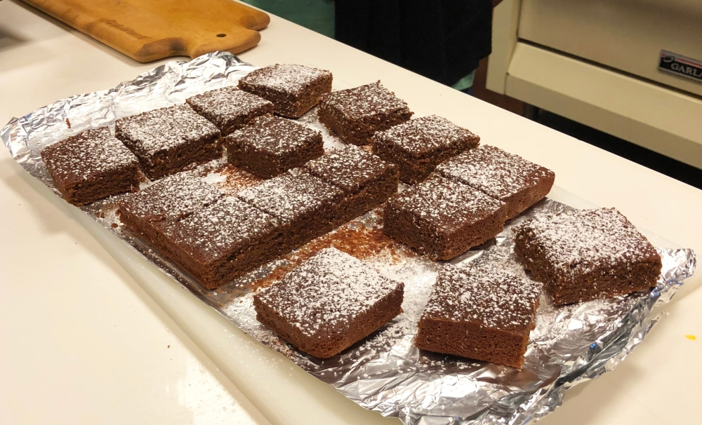 A tray full of brownie squares, made with Rio Luna Organic Peppers, topped with powdered sugar.