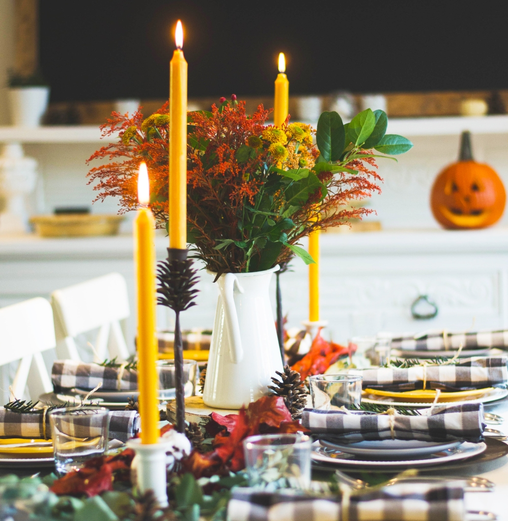 A beautiful Thanksgiving table set with candles and place settings ready for family and friends to enjoy breaking bread together.