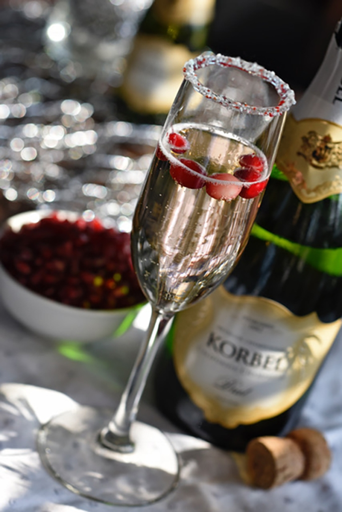 Dip the rim of a champagne flute in melted white chocolate, then dip in finely crushed candy cane. Pour crème de cacao into a champagne flute. Top with Korbel.