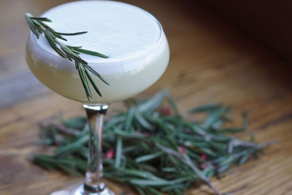Add egg white and gin in a Boston shaker and shake 5-6 times. Add in liqueur, lemon juice, rosemary syrup, and olive oil, then fill shaker with ice. Shake vigorously and strain in to a cocktail glass. Garnish with bitters and Rosemary sprig.
