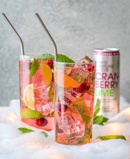 First, muddle mint and lime wedge into the bottom of a high ball glass. Then, add simple syrup followed by ice. Next, pour in cranberry juice and top off with Smirnoff Spiked Sparkling Seltzer Cranberry Lime. Finally, Garnish with fresh lime wedges, cranberries and mint leaves.