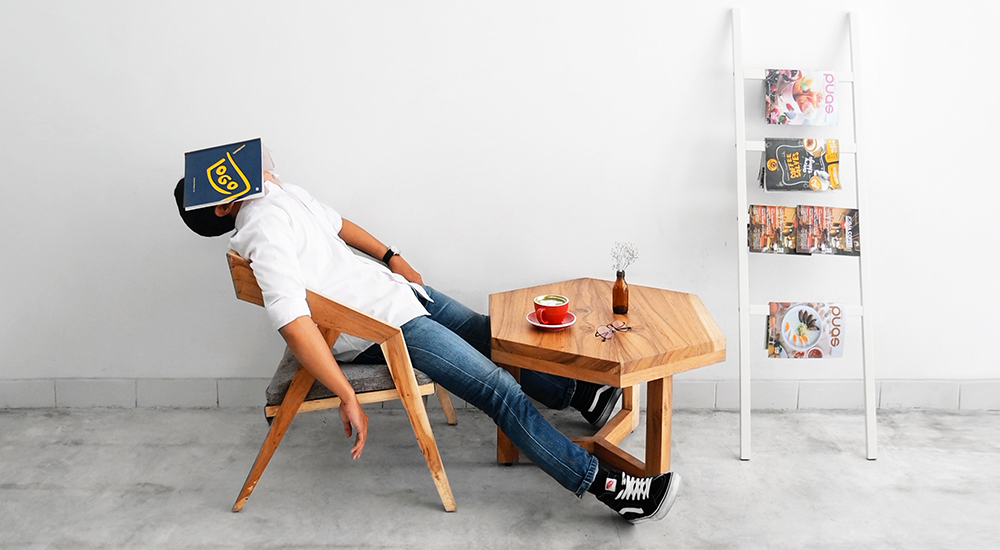 This man, sitting at a table, with a book over his face, is simply exhausted.