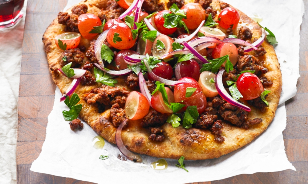 This recipe for Mediterranean Pizza with Grapes is a take on a classic pizza, made with naan. Filled with the protein of your choice browned and seasoned with tomato paste, olive oil, lemon juice, paprika and cayenne.