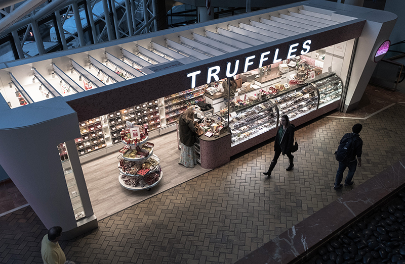 A truffle shop featuring an assortment of chocolate truffles for purchase.