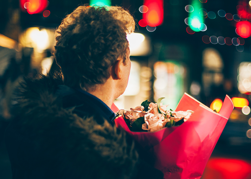 A man carries a bouquet of fresh flowers on his way to a date for Valentine's Day.