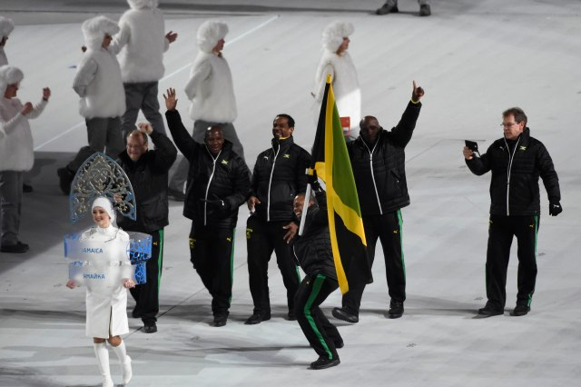 Jamaican flag bearer Marvin Dixon leads his country's Olympic team onto the stage during the opening ceremony for the Sochi 2014 Olympic Winter Games at Fisht Olympic Stadium. (Robert Hanashiro, USA TODAY Sports)