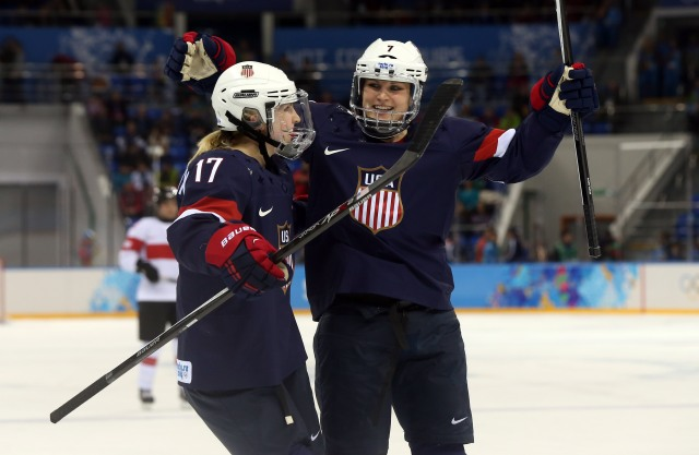 USA forward Monique Lamoureux (7) celebrates with forward Jocelyne Lamoureux (17) after scoring a goal against Switzerland in a women's preliminary round women's ice hockey game during the Sochi 2014 Olympic Winter Games at Shayba Arena. (Winslow Townson-USA TODAY Sports)