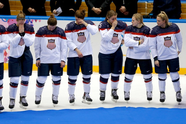 Members of the U.S. women's hockey team wipe tears away while waiting for their silver medals. (Winslow Townson, USA TODAY Sports)