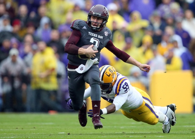 Texas A&M Aggies quarterback Johnny Manziel carries the ball in front of LSU Tigers defensive end Jermauria Rasco (59) in the first quarter at Tiger Stadium. (Crystal LoGiudice - USA TODAY Sports)