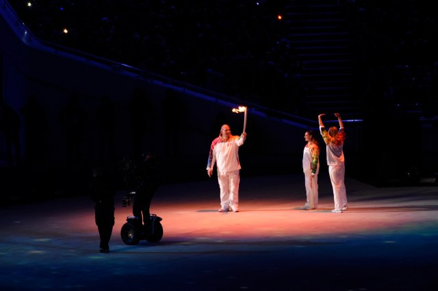 Torch bearer Alexander Karelin holds the Olympic touch during the opening ceremony for the Sochi 2014 Olympic Winter Games at Fisht Olympic Stadium. Also pictured is Maria Sharapova (right) and Elena Isinbeava (center). Mandatory Credit: Robert Hanashiro-USA TODAY Sports