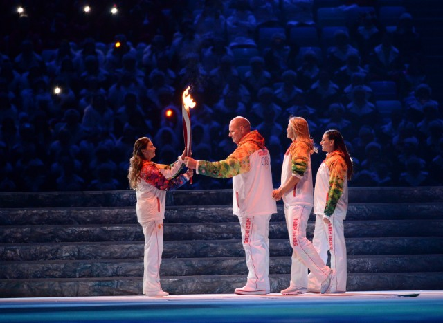 Alina Kabaeva, left, receives the torch from Alexandr Karelin during Opening Ceremony during the Sochi 2014 Olympic Winter Games . Mandatory Credit: Robert Deutsch-USA TODAY Sports