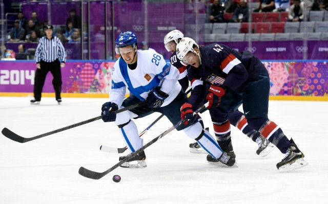 USA forward David Backes (42) reaches for the puck against Finland forward Jarkko Immonen (26) in the men's ice hockey bronze medal game during the Sochi 2014 Olympic Winter Games at Bolshoy Ice Dome. Scott Rovak-USA TODAY Sports.