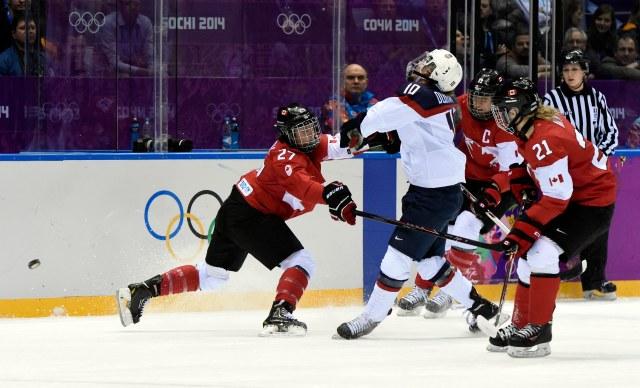 USA forward Meghan Duggan (10) is hit by Canada defenseman Tara Watchorn (27). (Scott Rovak, USA TODAY Sports)
