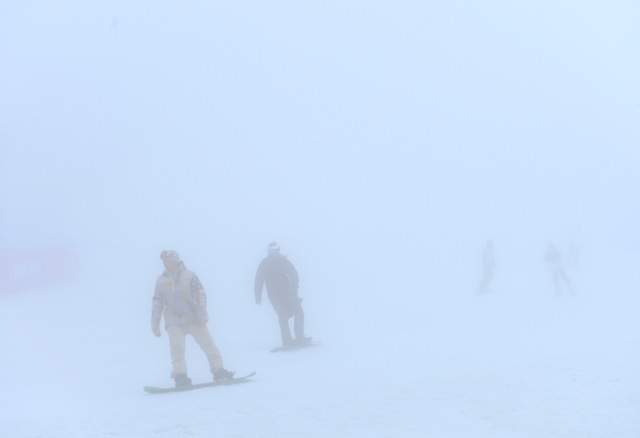 Snowboarders warm up in the fog at Rosa Khutor Extreme Park. (Jack Gruber, USA TODAY Sports)
