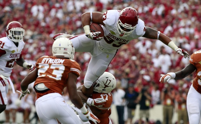 Oklahoma Sooners fullback Trey Millard jumps over Texas Longhorns safety Adrian Phillips during the Red River Rivalry at Cotton Bowl Stadium. (Tim Heitman - USA TODAY Sports)