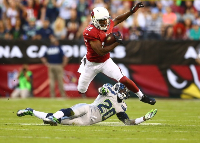 Arizona Cardinals wide receiver Andre Roberts  leaps over Seattle Seahawks cornerback Jeremy Lane at University of Phoenix Stadium. (Mark J. Rebilas - USA TODAY Sports)