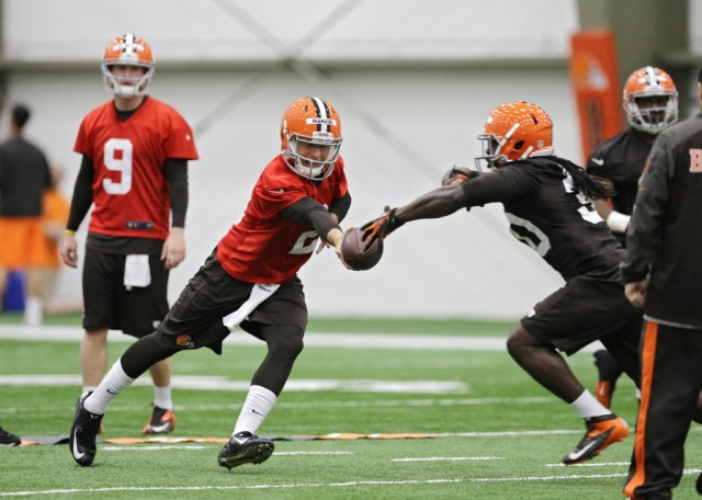 Cleveland Browns quarterback Johnny Manziel hands off during a rookie minicamp practice at the NFL football team's facility in Berea, Ohio. (Mark Duncan - Associated Press)