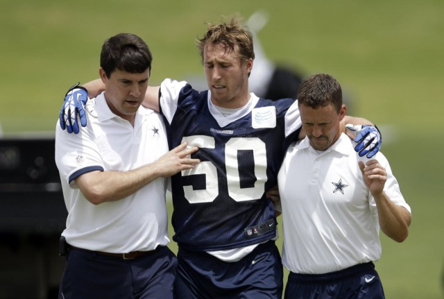 Dallas Cowboys linebacker Sean Lee is helped off the field by head athletic trainer Jim Maurer, left, and associate athletic trainer Britt Brown, right, after suffering an unknown left leg injury during an NFL football organized team activity, Tuesday, May 27, 2014, in Irving, Texas. (Tony Gutierrez - Associated Press)