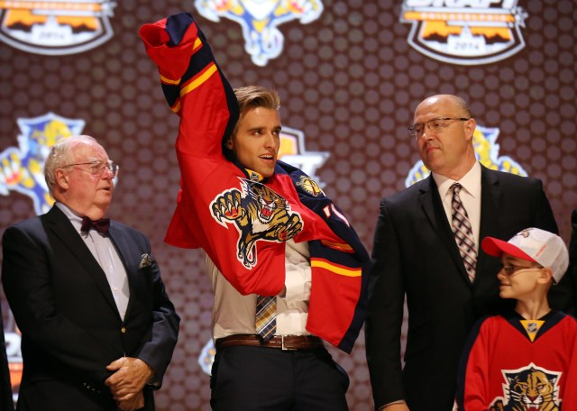 Aaron Ekblad puts on a team jersey after being selected as the number one overall pick to the Florida Panthers. (Bill Streicher, USA TODAY Sports)