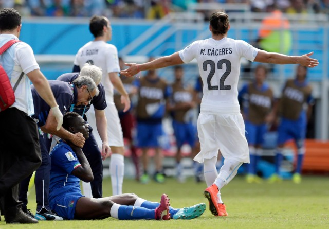 Medical personnel examine Italy's Mario Balotelli after his collision with Uruguay's Martin Caceres. (AP Photo/Petr David Josek)