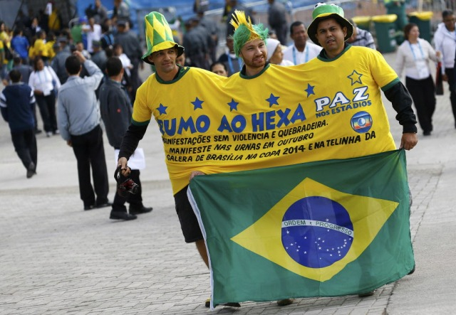 """Supporters of Brazil's national soccer team share shirt an oversized reading """"we go for the sixth Cup win"""" as they arrive for the opening match of the soccer World Cup between Brazil and Croatia at the Arena de Sao Paulo in Sao Paulo. (REUTERS/Kai Pfaffenbach)"""